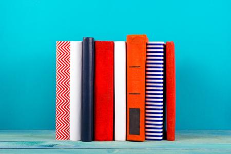 libros antiguos: Pila de libros de colores, fondo azul sucio, copia espacio libre de la vendimia viejos libros de tapa dura en el estante de madera sobre la mesa cubierta, sin etiquetas, la columna en blanco. De vuelta a la escuela. Antecedentes educacionales