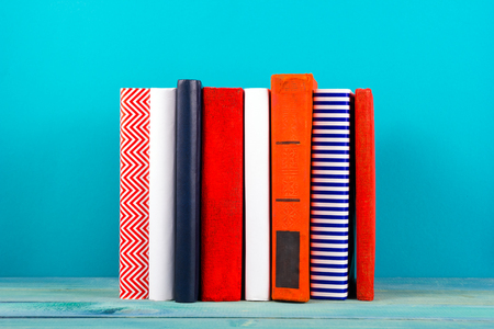 book: Stack of colorful books, grungy blue background, free copy space Vintage old hardback books on wooden shelf on the deck table, no labels, blank spine. Back to school. Education background