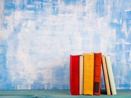 古いヴィンテージ カラフルなハードカバーの本、ウッドデッキのテーブルと芸術的な青い背景に日記で構成。スタッキングの本。学校に戻る領域を