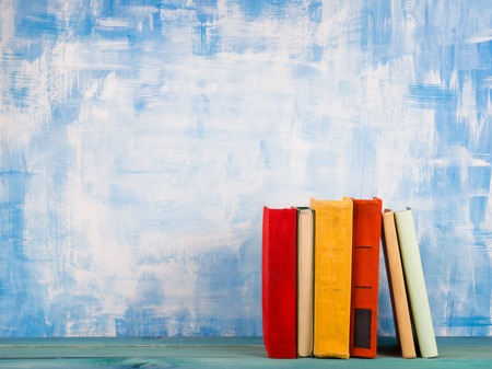 Composition with old vintage colorful hardback books, diary on wooden deck table and artistic blue background. Books stacking. Back to school. Copy Space. Education background Stockfoto