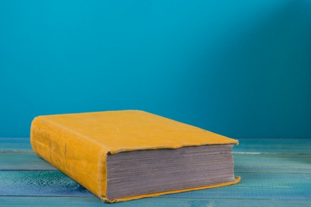 Stapel von bunten Bücher, grungy blauen Hintergrund, kostenlose Kopie Raum Jahrgang alten gebundene Bücher auf Holzregal auf dem Deck Tisch, keine Etiketten, leere Wirbelsäule. Zurück zur Schule. Bildungshintergrund