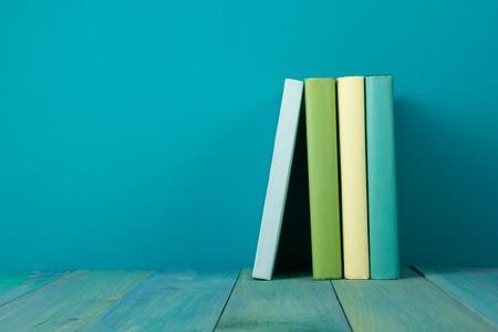 libros antiguos: Fila de libros, fondo azul sucio, copia espacio libre de la vendimia viejos libros de tapa dura en el estante de madera sobre la mesa cubierta, sin etiquetas, la columna en blanco. De vuelta a la escuela. Antecedentes educacionales