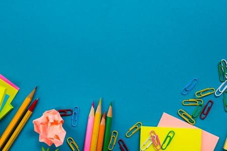 カラフルな供給、白い空白のメモ帳、カップ、ペン、pc、しわくちゃの紙のセットのオフィス テーブル デスクは、青の背景に花します。本文トップ