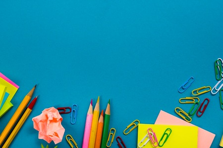 Office table desk with set of colorful supplies, white blank note pad, cup, pen, pc, crumpled paper, flower on blue background. Top view and copy space for text. Stock Photo