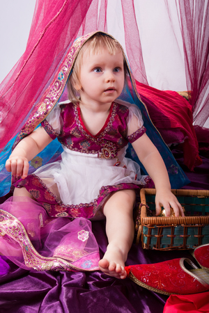 sultana: Little young east girl, sultana, Princess in Indian dress sari burqa scarf veil holding a pearl necklace sitting on a floor pillow at home interior under pink canopy. Childhood, copy space, doll house Stock Photo