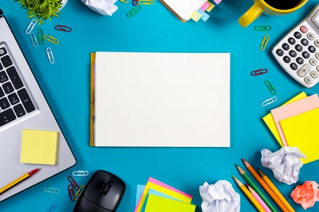 advertisment: Office table desk with set of colorful supplies, white blank note pad, cup, pen, pc, crumpled paper, flower on blue background. Top view and copy space for text. Stock Photo