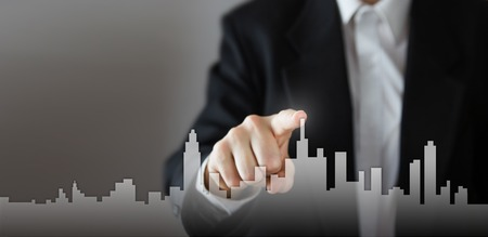 Businessman Activate Growth Process, choosing house, real estate city concept. Skyline Hand pressing the house icon on virtual screen. Business, technology, internet and networking concept. Copy space. Foto de archivo
