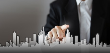 Businessman Activate Growth Process, choosing house, real estate city concept. Skyline Hand pressing the house icon on virtual screen. Business, technology, internet and networking concept. Copy space. Stockfoto