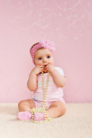 rubbing noses: Little girl sitting on the floor holding a pearl necklace.
