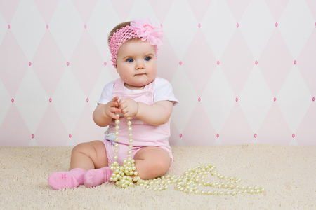 rubbing noses: Little girl sitting on the floor holding a pearl necklace
