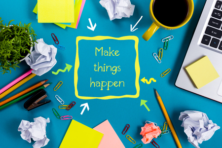 happens: Make things happens. Office table with notepad, computer and coffee cup on blue background. Business creative consept top view