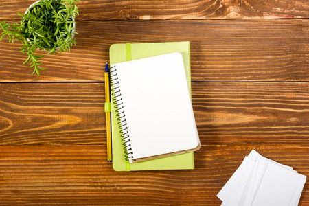 note pad: Office table desk with set of colorful supplies, white blank note pad, cup, pen, pc, crumpled paper, flower on wooden background. Top view and copy space for ad text.