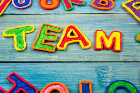 Word TEAM made with plasticine letters on old wooden blue board background