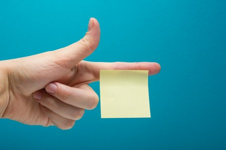 Hand holding yellow note reminder on finger with copy space for ad on blue background Stock Photo