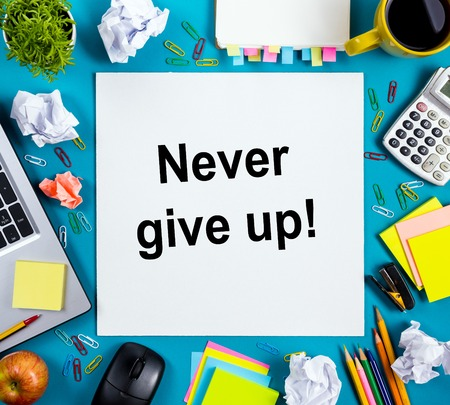 faq's: Never give up. Office table with notepad, computer and coffee cup on blue background. Business creative consept top view Stock Photo