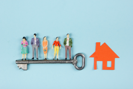 finance concept: Real Estate concept. Construction building. People toy figures, paper model house with key on blue architect desk table background. Top view. Copy space for ad text