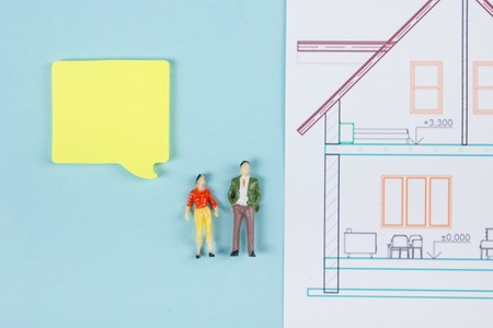 architectural firm: Real Estate concept. Construction building. Blank speech bubbles, people toy figures, paper model house, blueprints with key on blue architect desk table background. Top view. Copy space for ad text