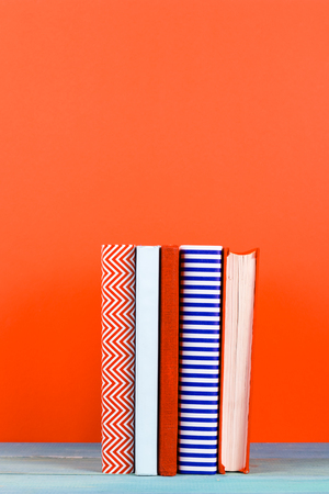 fanned: Composition with vintage old hardback books, diary, fanned pages on wooden deck table and red background. Books stacking. Back to school. Copy Space. Education background.