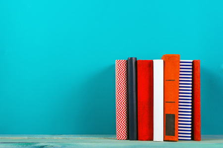 free education: Stack of colorful books, grungy blue background, free copy space Vintage old hardback books on wooden shelf on the deck table, no labels, blank spine. Back to school. Education background