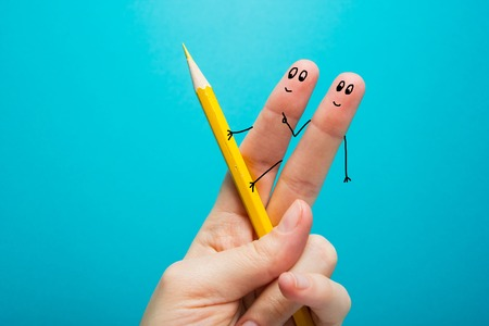 percolate: Funny fingers drawing holding yellow pencil against blue background. Conceptual motivation picture.