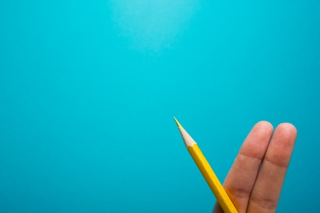 Funny fingers drawing holding yellow pencil against blue background. Conceptual motivation picture.
