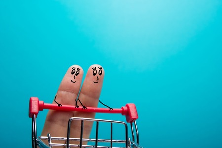 Funny fingers shopping at supermarket with red trolley on blue background. Stock Photo