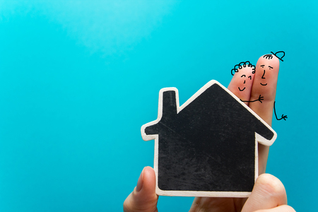 fingers on top: Hand with funny fingers holding white paper house figure on blue background. Real Estate Concept. Copy space top view