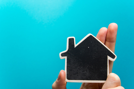 people, charity, family and home concept - close up of woman holding blackboard paper house cutout against blue background.