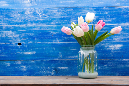Beautiful pink flowers tulips on blue wooden desk table. Copy space. Stock Photo