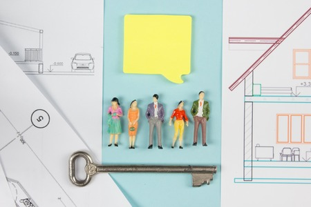 neighbours: Real Estate concept. Construction building. Blank speech bubbles, people toy figures, paper model house, blueprints with key on blue architect desk table background. Top view. Copy space for ad text