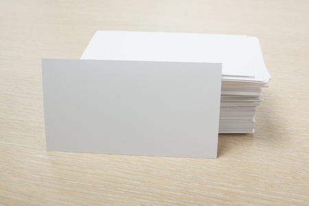 White blank business card. Office table desk with set of colorful supplies, cup, pen, pencils, flower, notes, cards on beige desk table background. Top view and copy space for ad text.