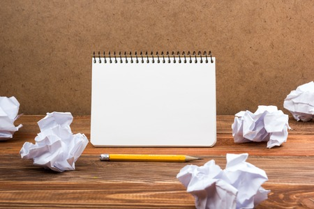Searching an idea, motivation, result, dwaing scetches. White blank notepad book at office worplace crampled paper notes on wooden grunge background. Copy space for ad text Stock Photo