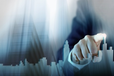 Businessman Activate Growth Process, choosing house, real estate city concept. Skyline Hand pressing the house icon on virtual screen. Business, technology, internet and networking concept. Copy space Stock Photo