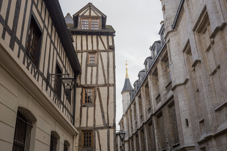 Old and tilted houses at Rue Eau de Robec in Rouen on a rainy day. Rue Eau-de-Robec is one of the main tourist streets of Rouen. Upper Normandy, France.