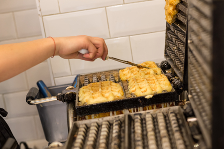 Cooking Belgian waffles in bakery - food background. Gaufres au sucre