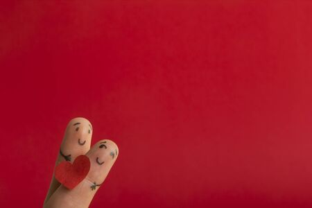 Valentines day fall in love concept. Painted happy funny fingers smiley holding red heart against red background with copy space for ad text Foto de archivo - 134777909