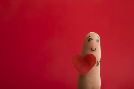 Valentines day fall in love concept. Painted happy funny fingers smiley holding red heart against red background with copy space for ad text Foto de archivo - 134777911