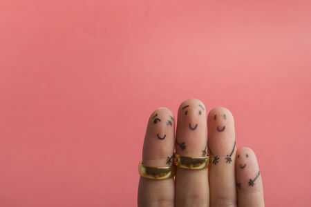 Painted happy fingers smiling in love against pink background with copy space for ad text. Marriage wedding rings Foto de archivo - 134777929