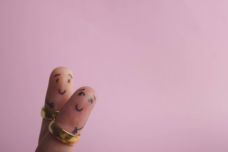 Painted happy fingers smiling in love against pink background with copy space for ad text. Marriage wedding rings Foto de archivo - 134778053