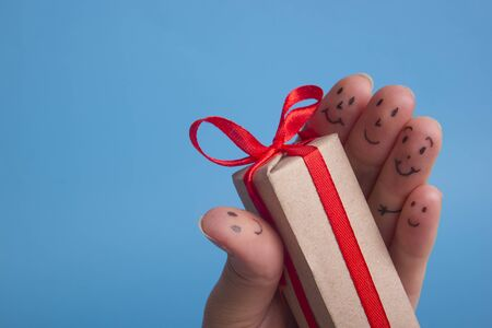 Funny fingers holding present gift box against blue background. Happy family celebrating concept for Christmas or New Years day