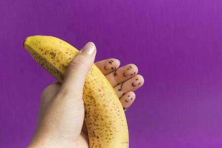 Painted funny fingers smiley holding yellow banana against purple background 写真素材