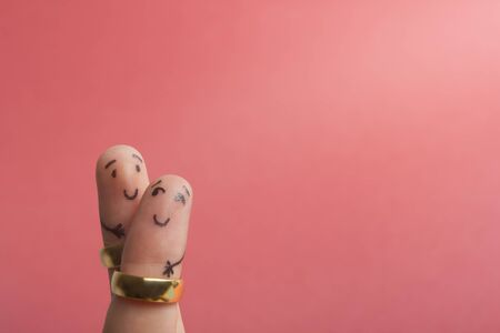 Painted happy fingers smiling in love against pink background with copy space for ad text. Marriage wedding rings