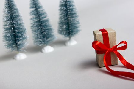 Christmas present gift box with red ribbon on white background and christmas tree. Copy space for text. Selective focus. 写真素材