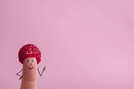 Funny fingers faces in hat raspberries berry against pink background. Happy family couple healthy eating concept.