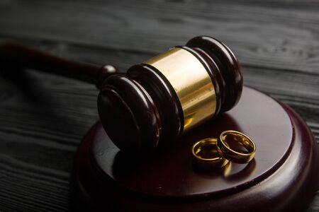 Divorce and separation concept. Two golden wedding rings, judge gavel. 写真素材