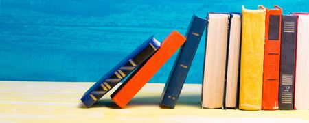 Composition with vintage old hardback books, diary, fanned pages on wooden deck table and abstract background. Books stacking. Back to school. Copy Space. Education background.