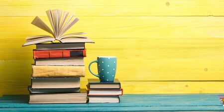 Composition with vintage old hardback books, diary, fanned pages on wooden deck table and red background. Books stacking. Back to school. Copy Space. Education background Фото со стока
