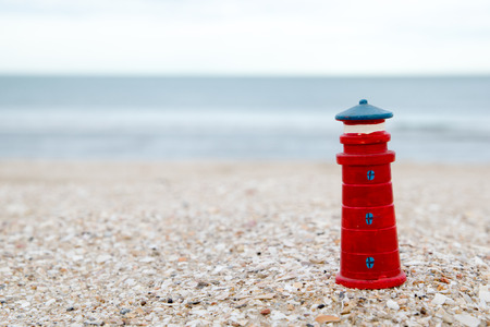 likable: cute lighthouse figure on the beach in the evening