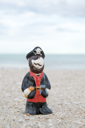 likable: cute pirate ceramic doll on beach Stock Photo