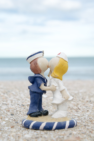 likable: old cute sailor and nurse doll on beach